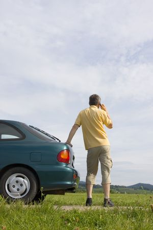Man talking on cell phone beside his car which has a breakdown or a empty fuel tank Stock Photo - 3413659