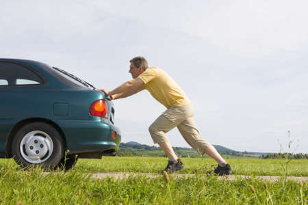 Man pushing a car with empty gas tank Stock Photo