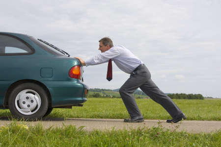 Businessman pushing a car with empty fuel tank Stock Photo