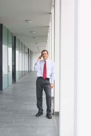 Businessman talking on mobile phone outside an office building photo