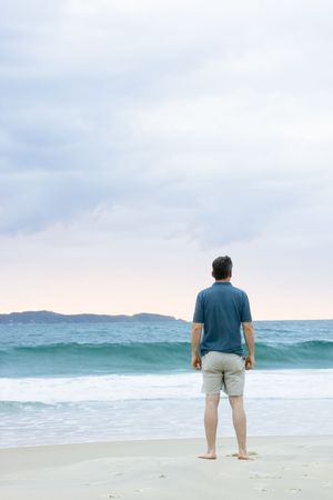 blue sky thinking: Man standing on the beach contemplating the sea