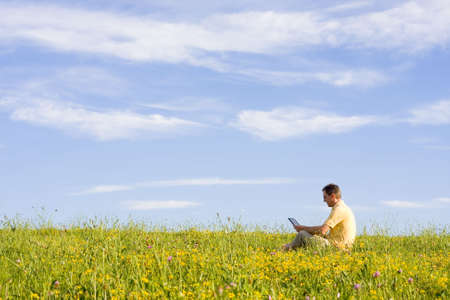 Man working with laptop in a meadow of flowers Stock Photo