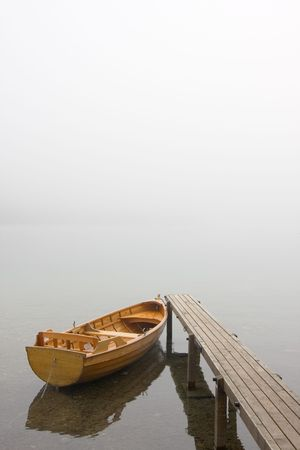 Boat at a landing stage of a lake on a misty morning Stock Photo