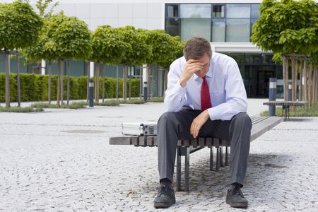 Sorrowful businessman sitting on a bench in front of an office building Stock Photo