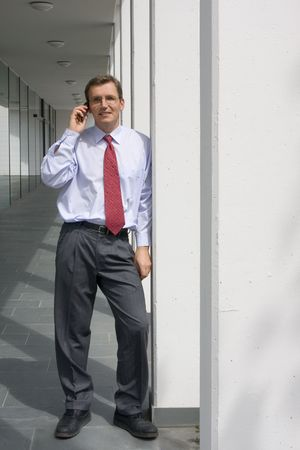 Businessman talking on mobile phone at aa office building photo