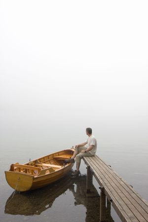 landing stage: Man sitting on a landing stage at a misty morning in fall