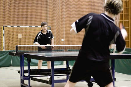 Two persons playing table tennis. Focus on the net of the table. Stock Photo