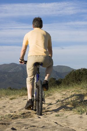 Man riding bicycle on the beach with hills in the background photo