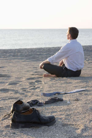 man meditating: Businessman relaxing on beach - Focus on the shoes in the foreground