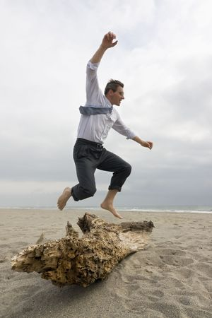 Businessman jumping over a tree trunk on a beach photo