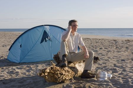 Man sitting in front of his tent on a beach while making a phone call Stock Photo - 4903057