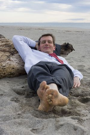 Businessman sleeping on a beach with a smile on his face photo