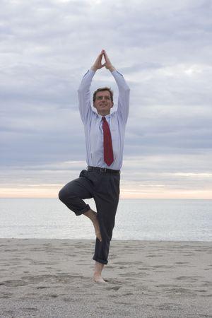 Businessman doing yoga on a beach photo