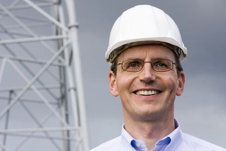 Smiling engineer with hardhat on construction site Stock Photo