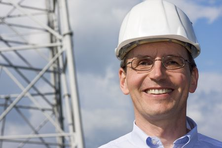 Smiling engineer with hardhat on construction site photo