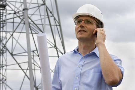 supervisores: Ingeniero de hablar por tel�fono m�vil en el lado de la construcci�n