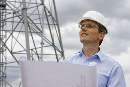 Engineer with blueprint in front of crane Stock Photo - 5469573