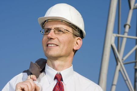 Smiling engineer with white hardhat on construction site