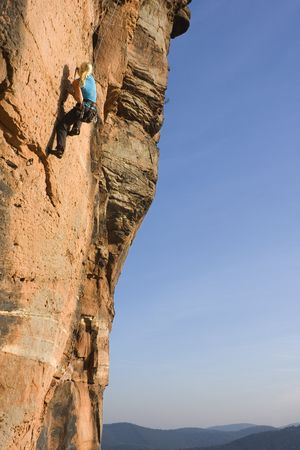Young woman climbing a rock of sandstone Stock Photo - 5755455