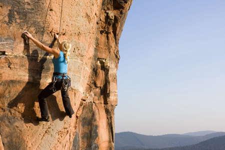 bergbeklimmen: Jonge vrouw die een rots van zand steen klimmen Stockfoto