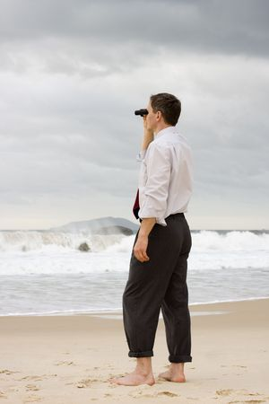 Businessman standing on a beach and searching with binoculars photo