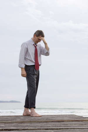 Depressed or worried businessman standing barefoot at the sea photo