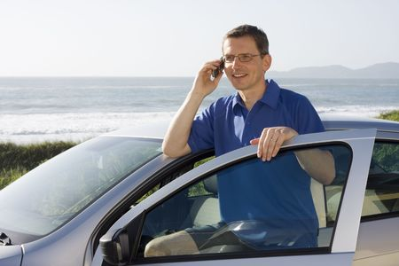 Man talking on cell phone beside a car at the sea photo