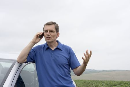 Angry man talking on cell phone beside a car Stock Photo - 6367492