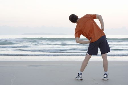 mature men: Runner doing stretching exercises on a beach early in the morning Stock Photo