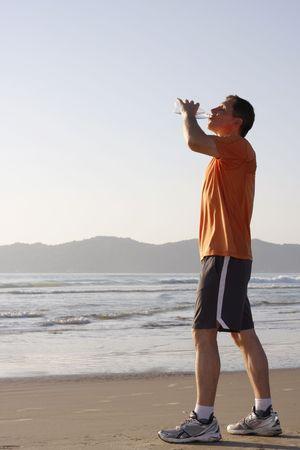 Runner drinking water on a beach photo