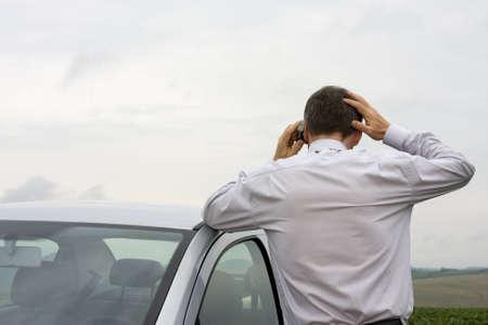 in trouble: Empresario preocupado, hablando por tel�fono celular al lado de su autom�vil