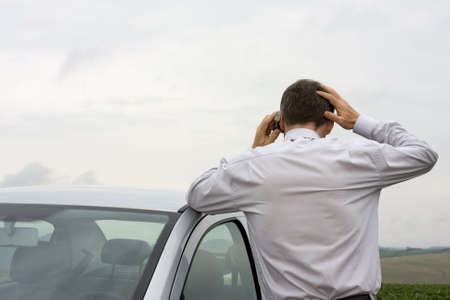 Worried businessman talking on cell phone beside his car photo