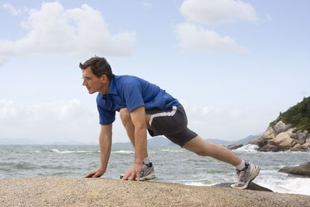 Jogger doing fitness exercises on a rock at the sea photo