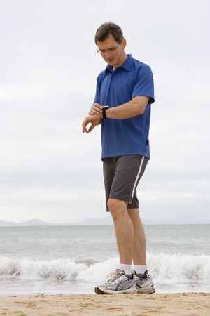 Runner looking at stop watch on a beach photo