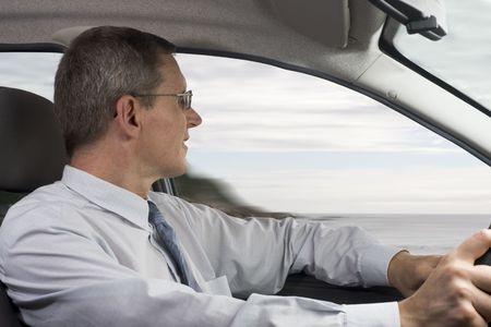 Businessman driving a car at the sea Stock Photo