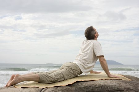 Mature man doing yoga exercises on a rock at the sea photo