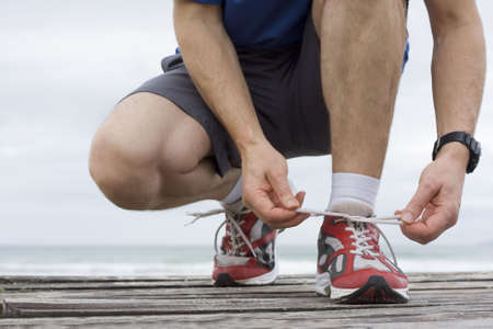 shoe laces: Runner tying shoelace in front of the sea