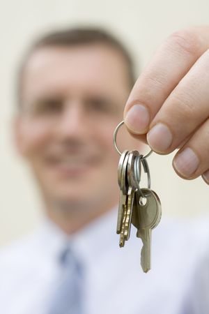 Smiling businessman handing over keys photo