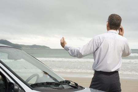 Businessman talking on cell phone beside his car on a beach photo