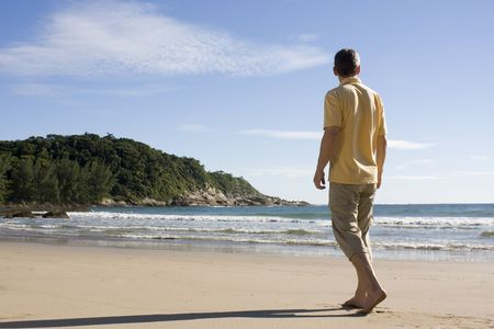 Mature man walking barefoot on a tropical beach in Brazil photo