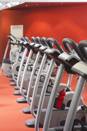 Bicycles in a row in a gym with red background and floor photo