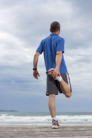 people jogging: Corredor haciendo ejercicios de estiramiento en una playa