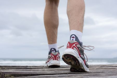 Details of feet of runner in front of a beach photo