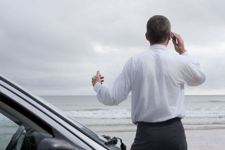 Businessman talking on mobile phone beside his car on a beach photo