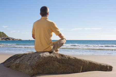 Man sitting on a rock at the beach and meditating Stock Photo