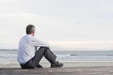 hombre pensando: Empresario pensativo sentado en una playa y mirando el mar Foto de archivo