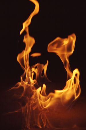 heat radiation: flames dancing in the dark Stock Photo
