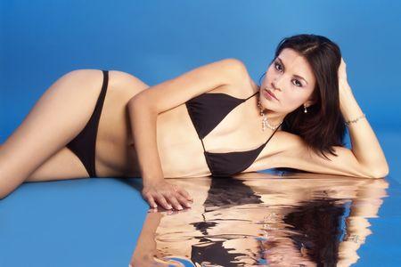 sexy brunette in black bikini lied down on blue reflection                     photo