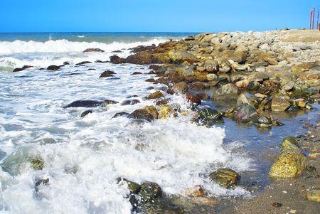 braking: Rocks at the beach braking waves                   Stock Photo