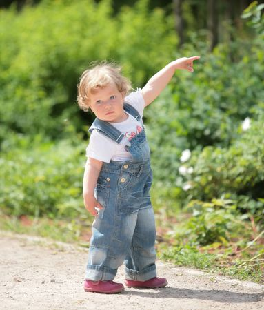 indicates: little girl in turn blue overalls indicates hand in wood